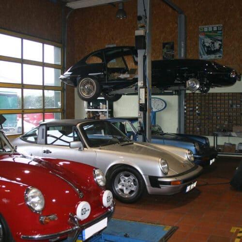 Kamps Classics - Werkstattservice alter Jaguar auf Hebebühne mit 3 Porsche